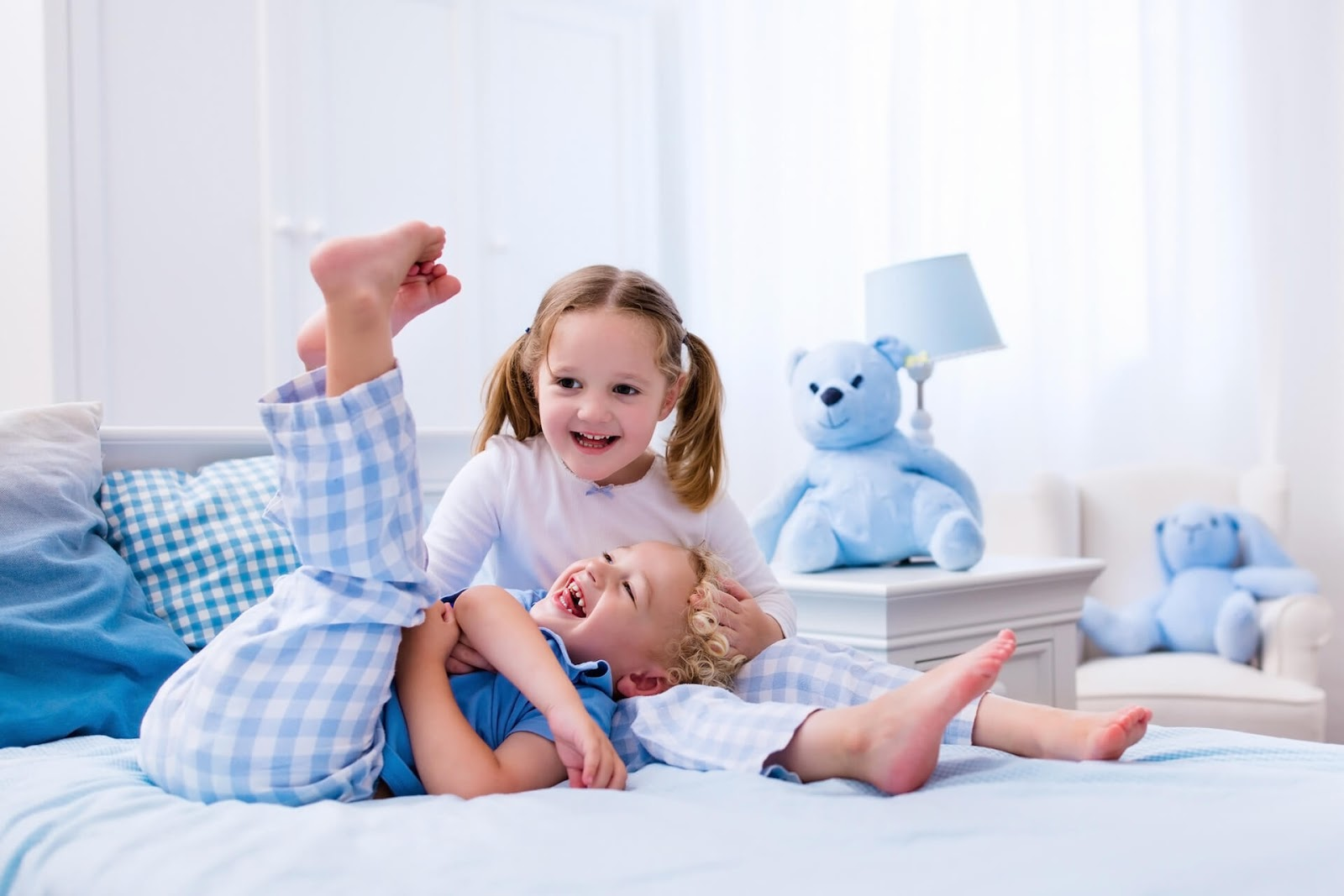 Children playing in bed in their jammies