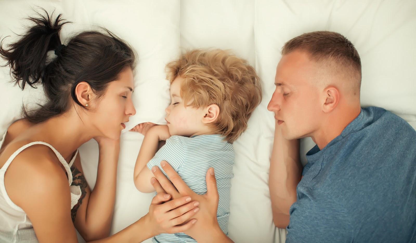 Child sleeping in bed between parents