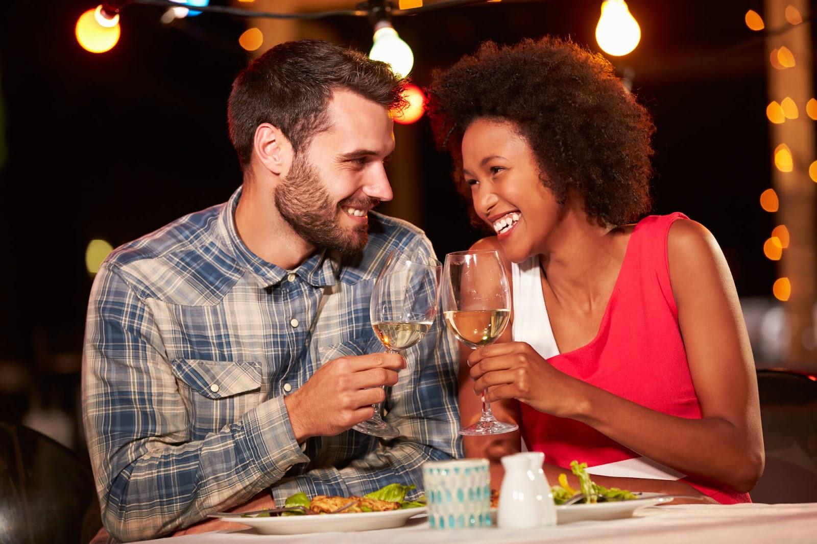 Man and woman eating at a restaurant and having fun