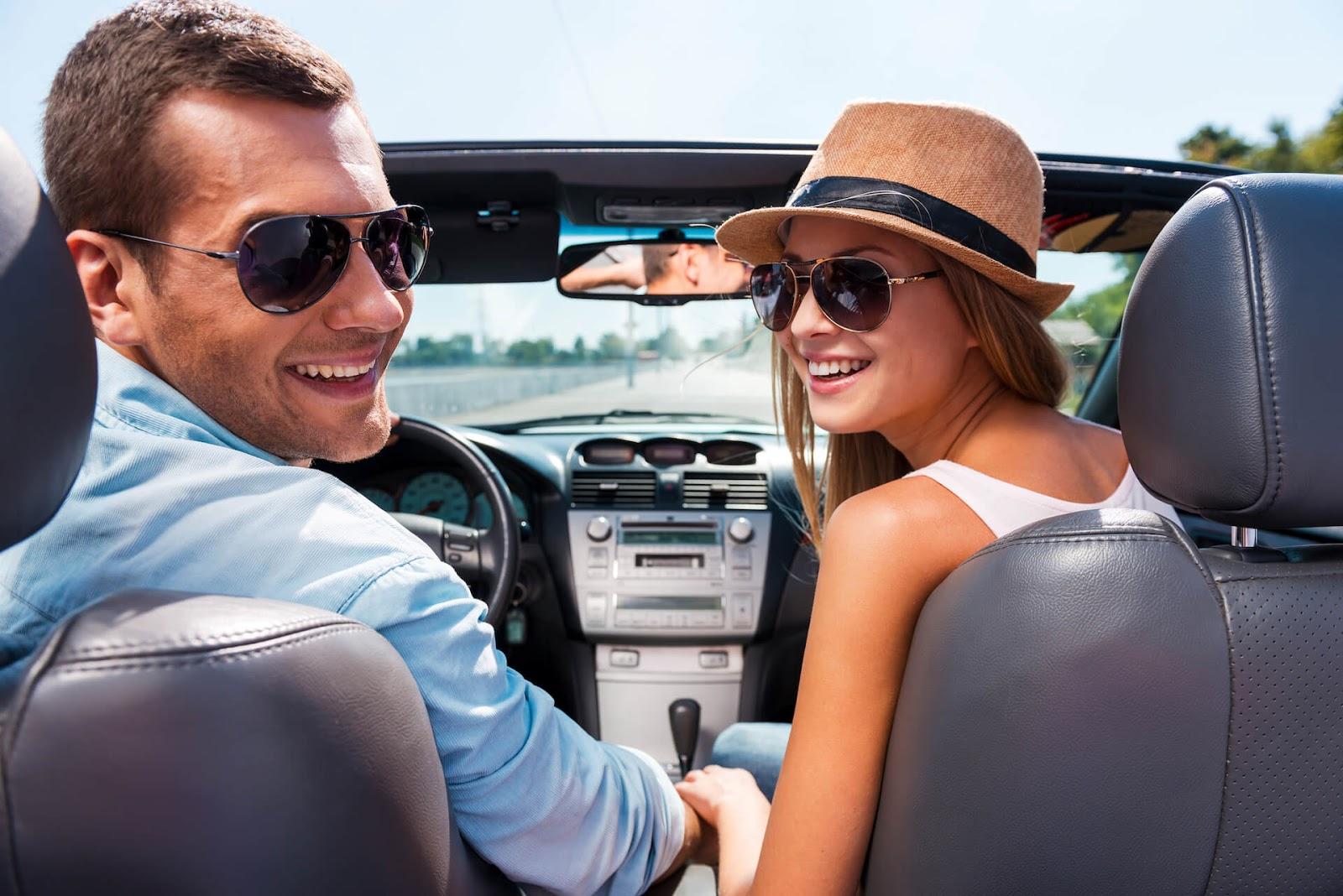 Man and woman enjoying a convertible car rental on vacation