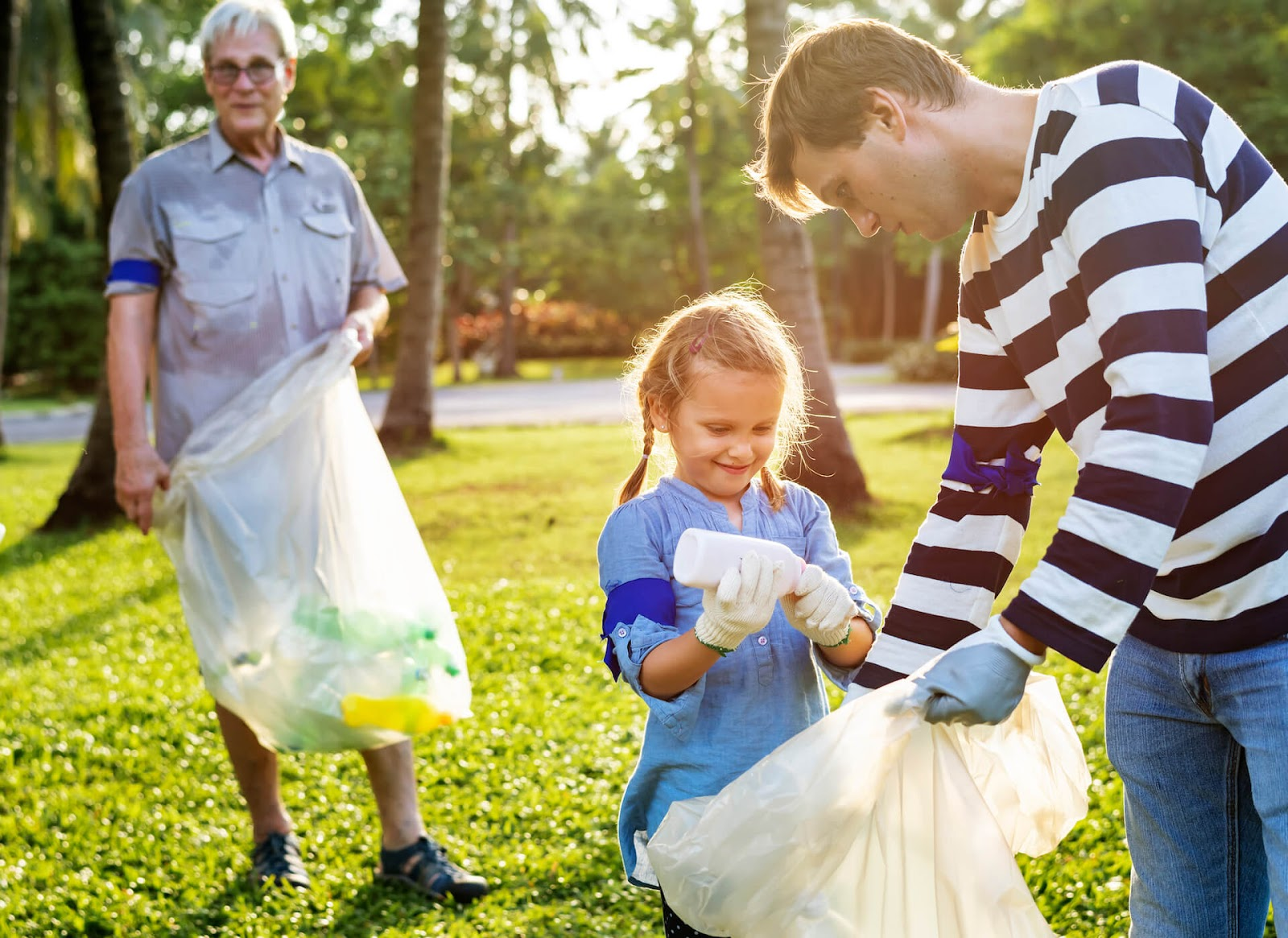 Man helping his daughter pick up trash in the park