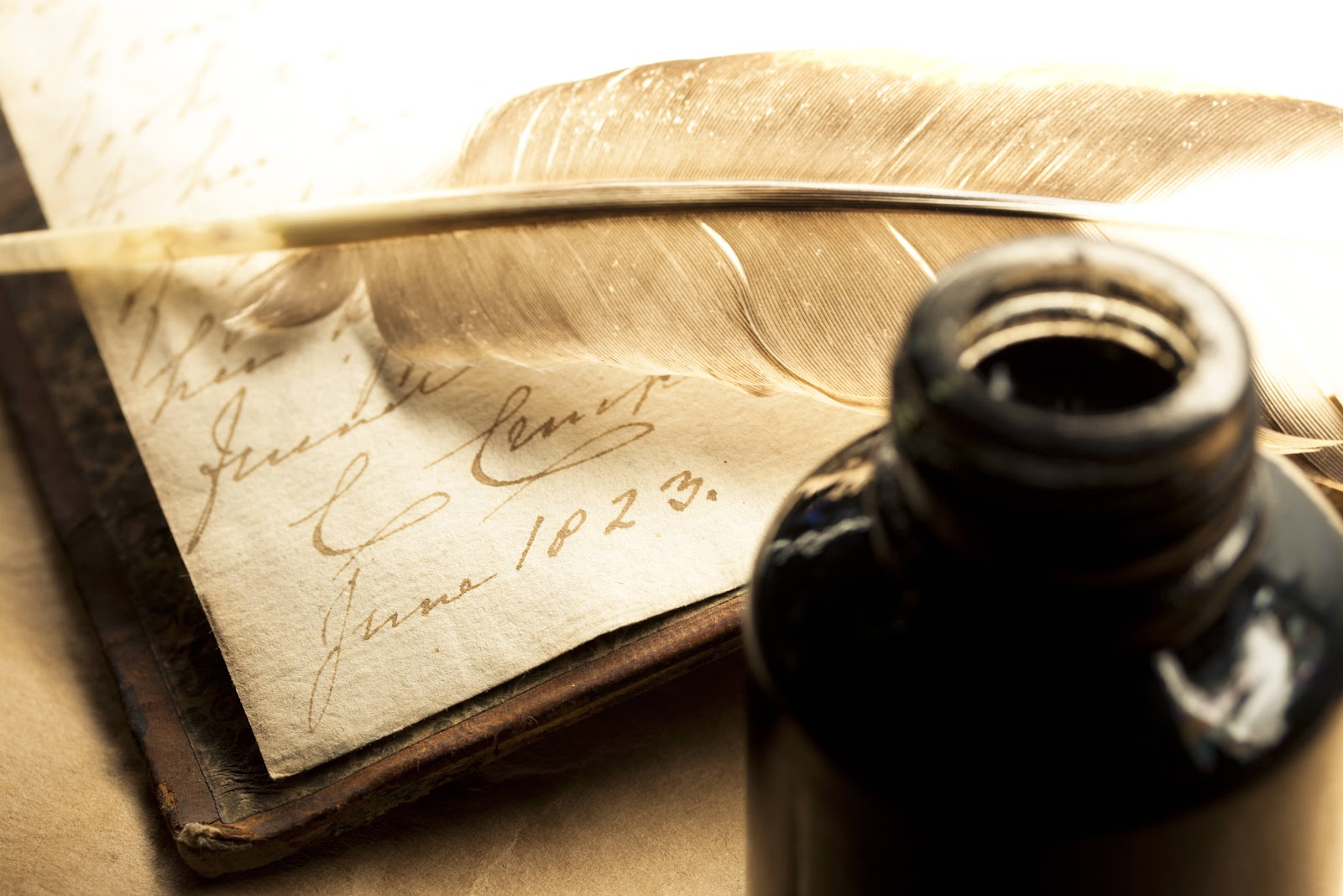 Feather quill and ink bottle with parchment