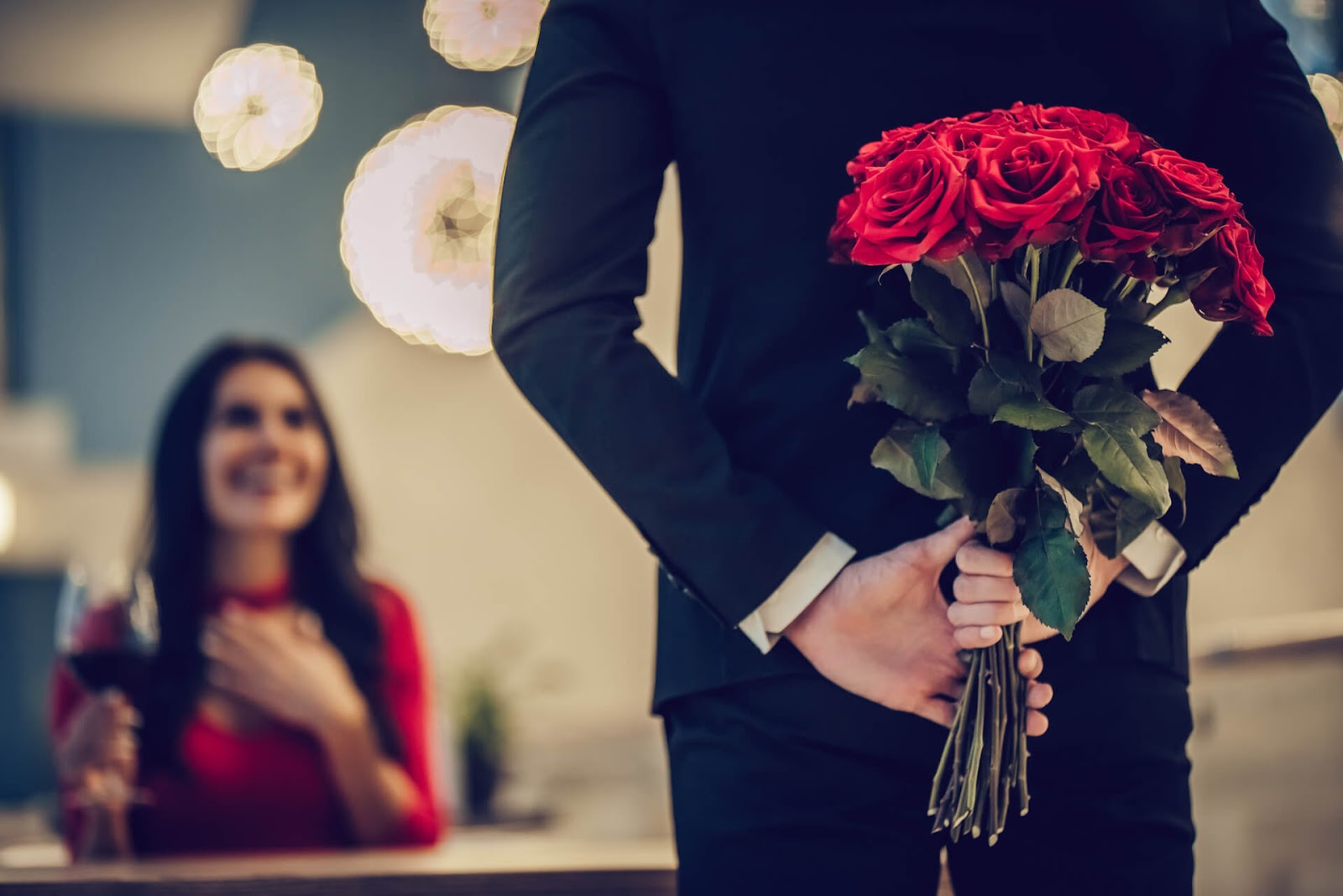 Man surprising a woman with red roses