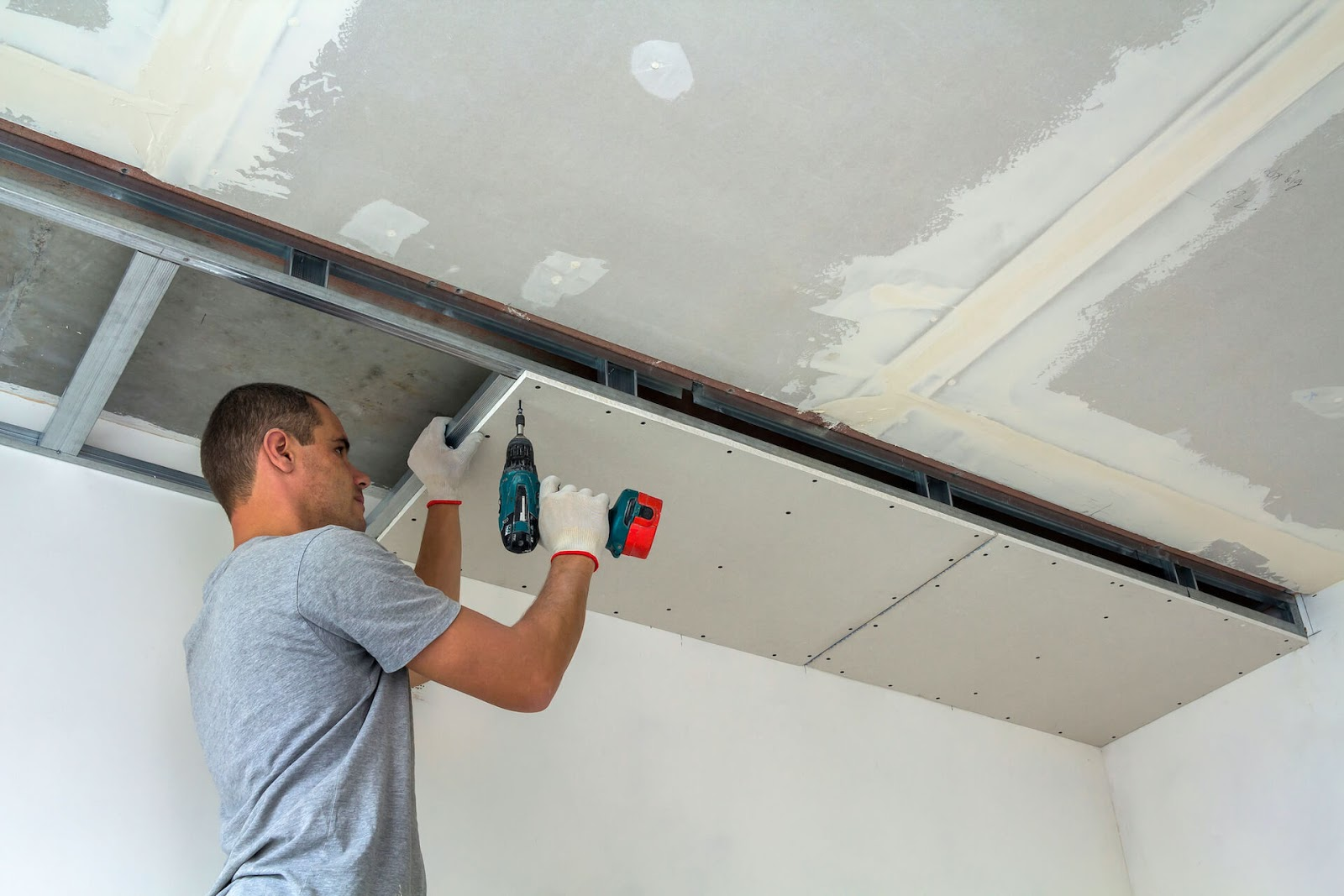 Man drilling dryall onto his ceiling