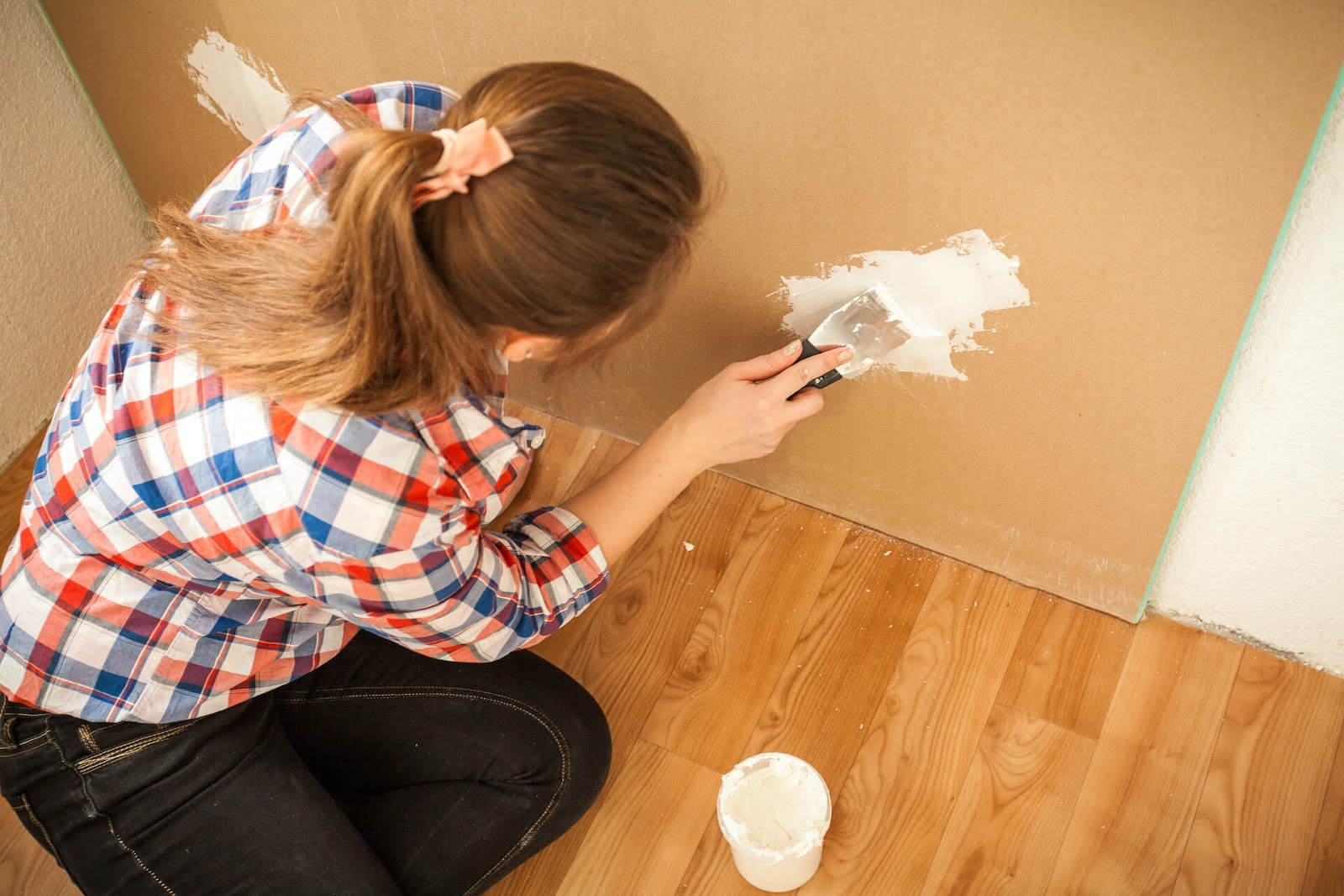 Woman spackling holes in her wall