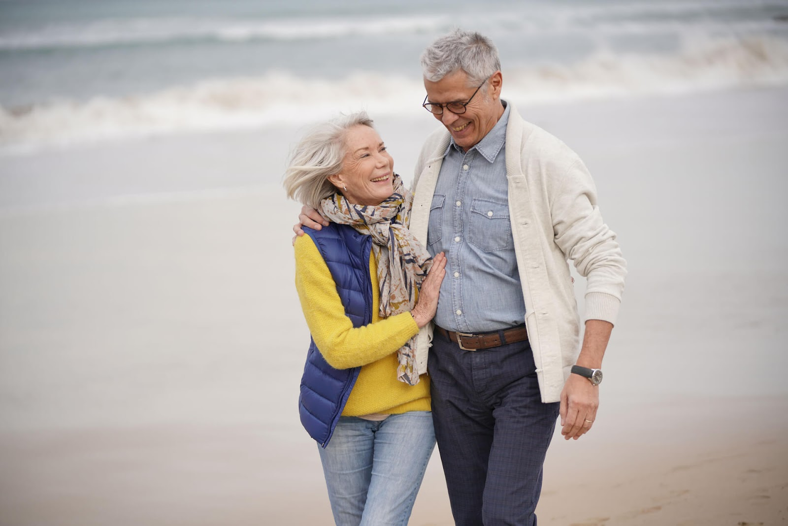 Man and wife walking down the beach together