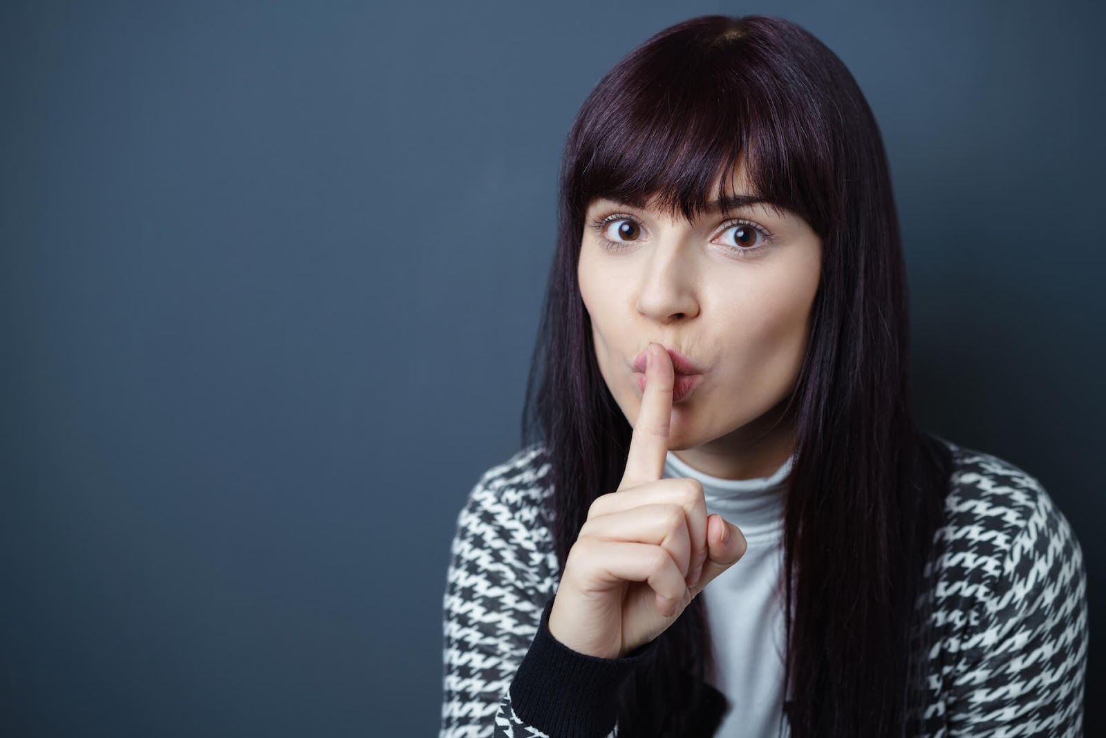Woman holding her finger up to her mouth