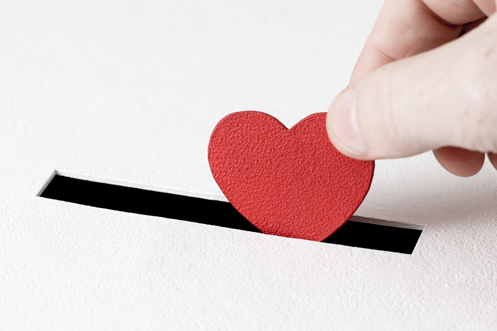 Hand putting a red heart in a box