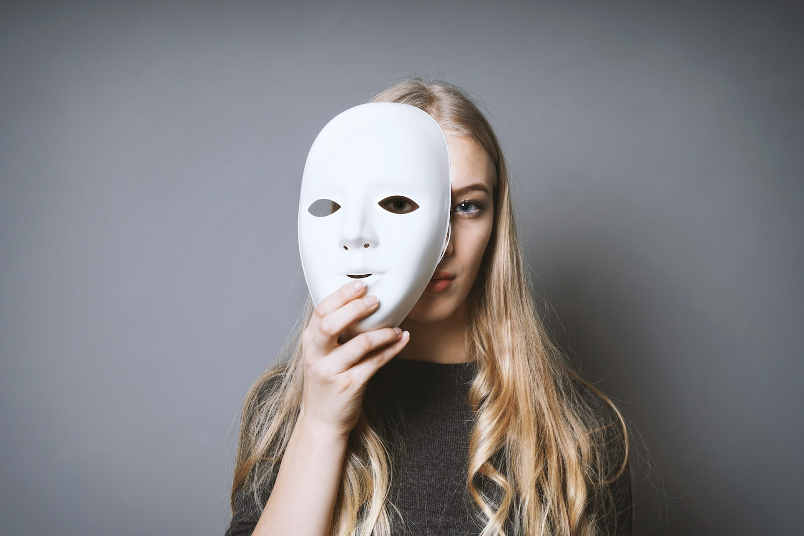 Woman hiding behind a mask