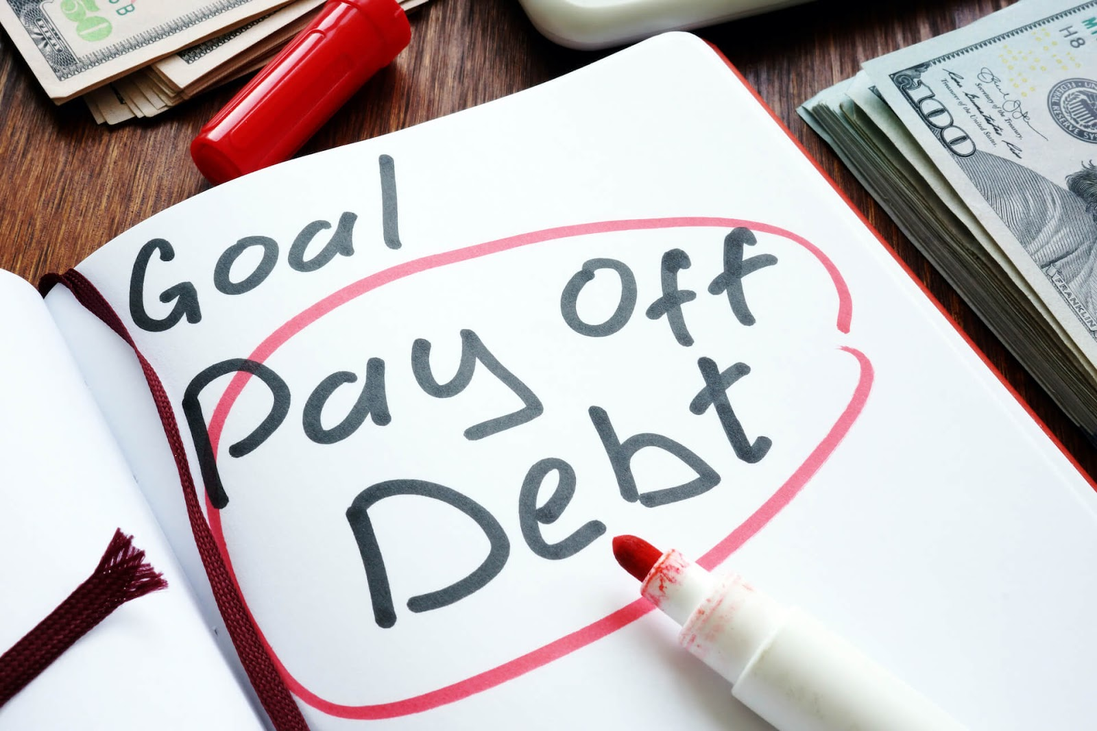 """""""Pay off debt"""" written in a goal book with some money laying around it"""