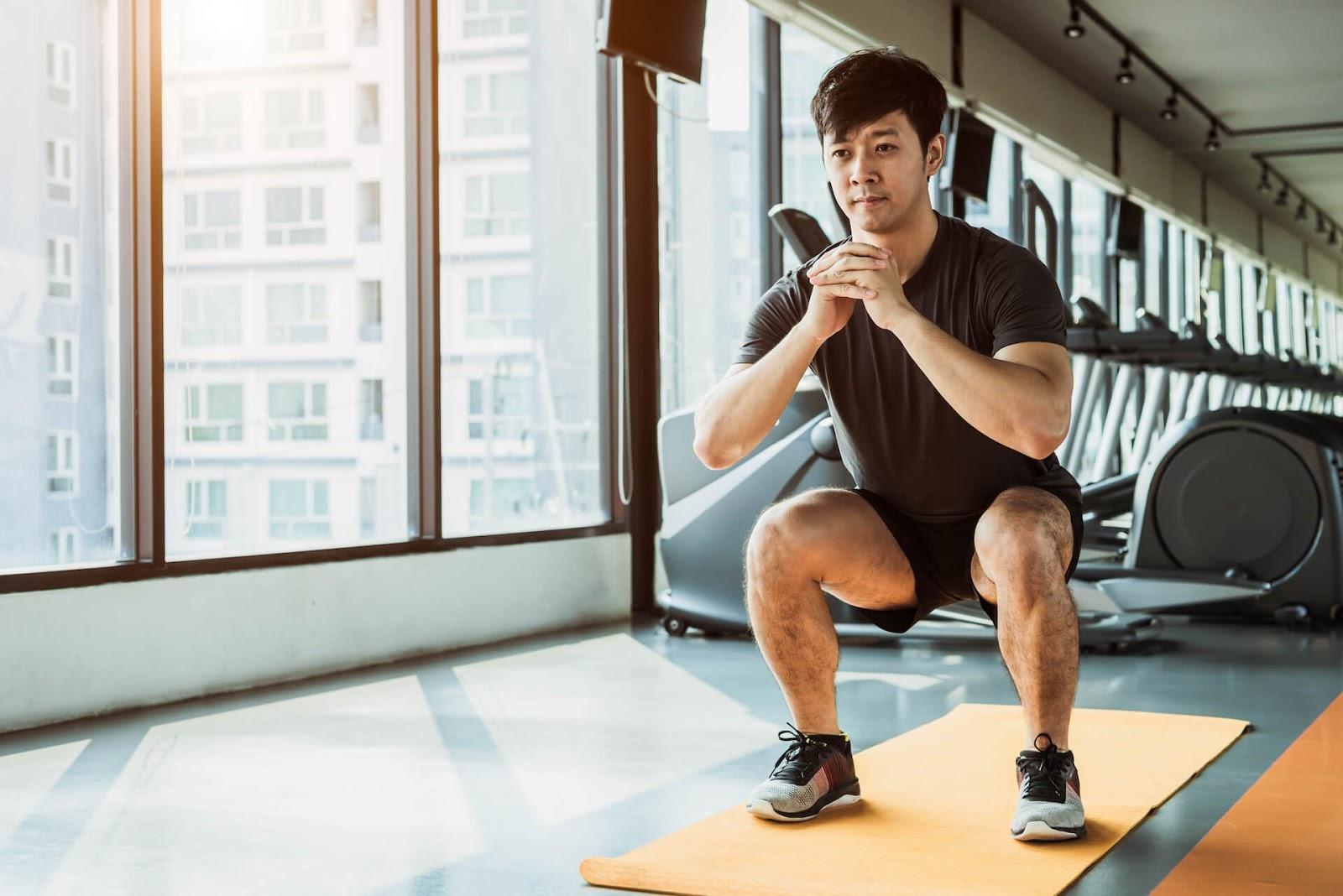 Man Squatting in a gym