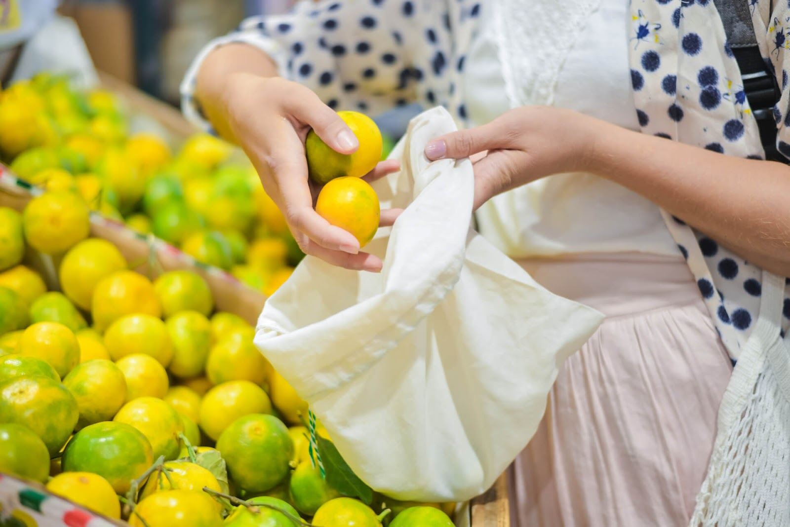 Woman putting lemons in her reusable shopping bag