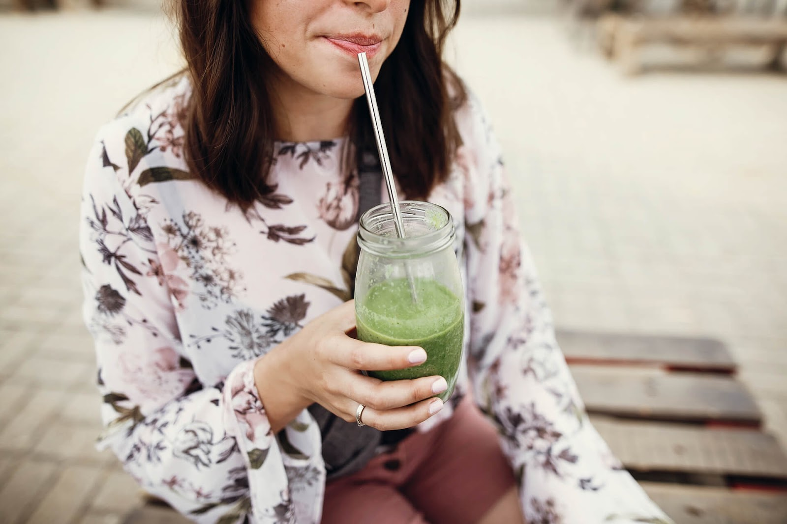 Woman drinking a green smoothie with a metal straw