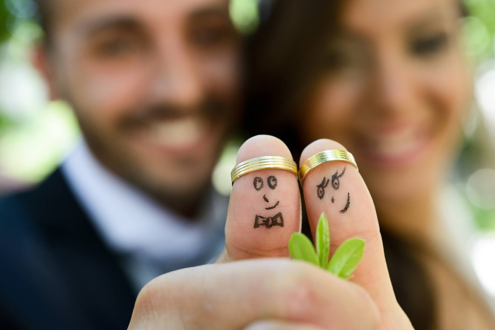 Bride and groom with rings on their thumbs & a face drawn on