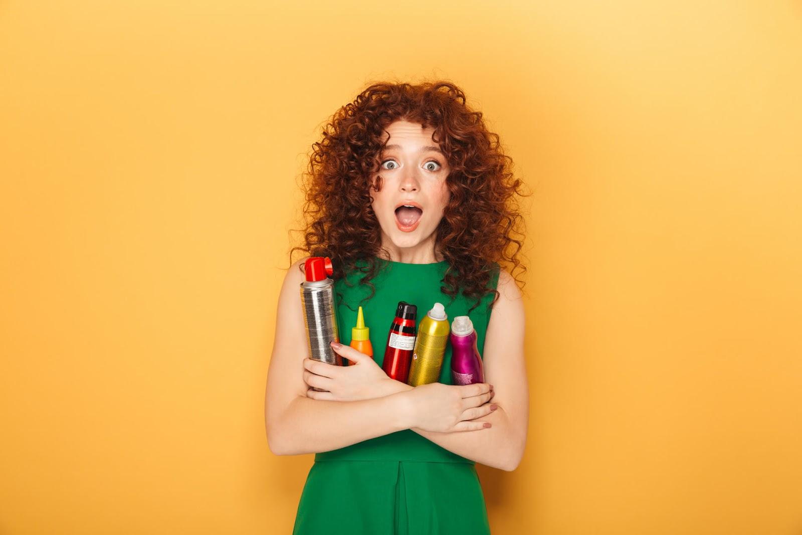 Curly-haired woman holding onto her hair products that aren't curly girl method approved
