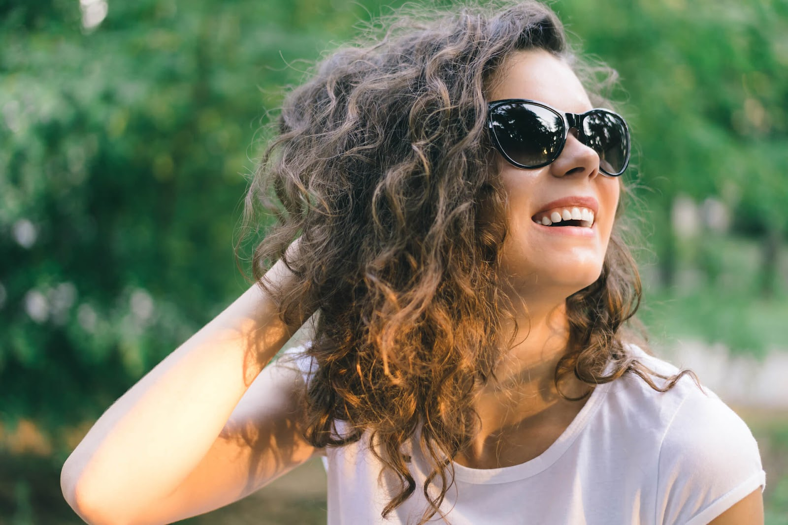 Curly-haired woman smiling in the sun