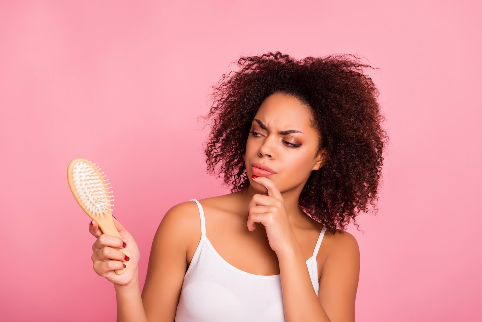 Woman looking suspiciously at her brush