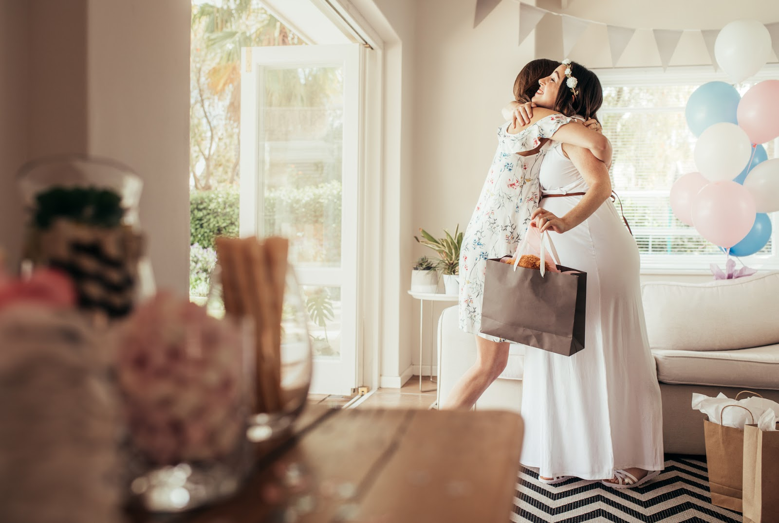 Woman hugging her pregnant friend at her baby shower