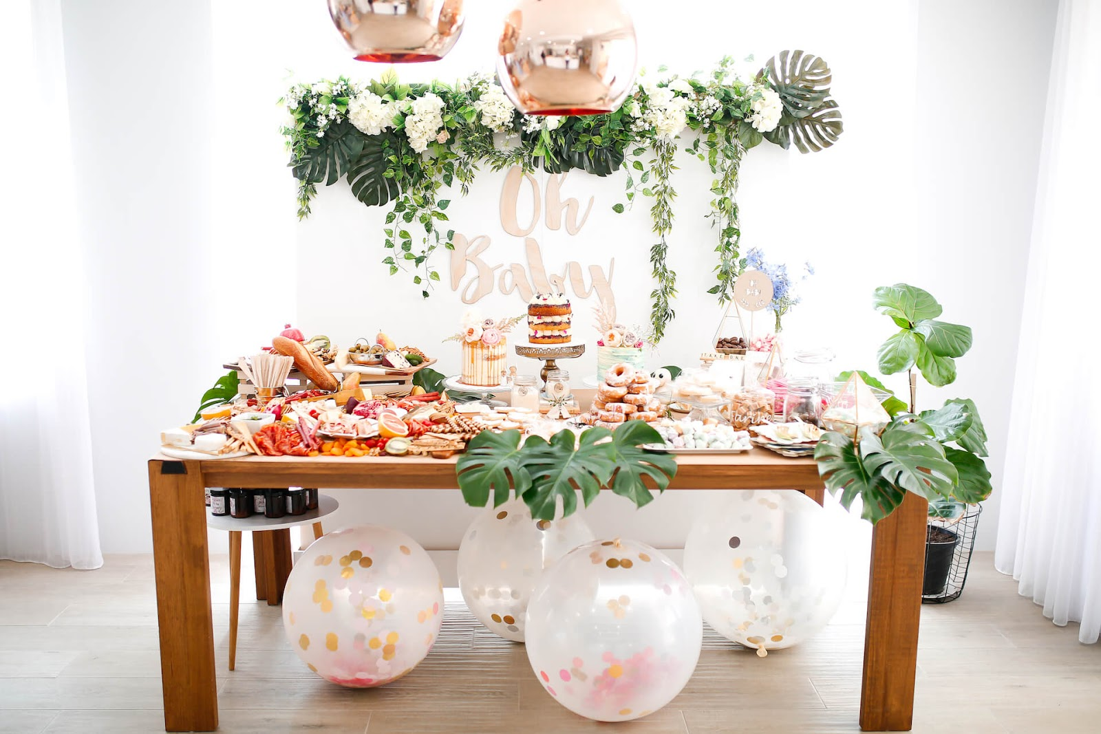 Baby shower food table with greenery around it