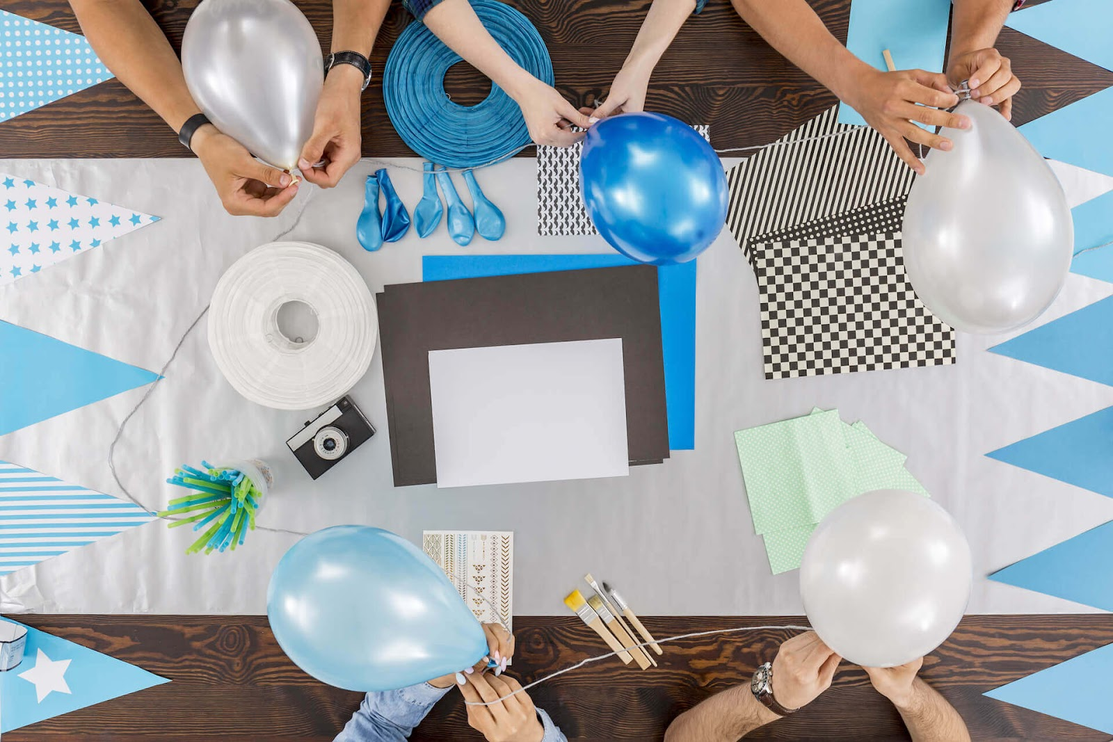 Hands blowing up and tying balloons together