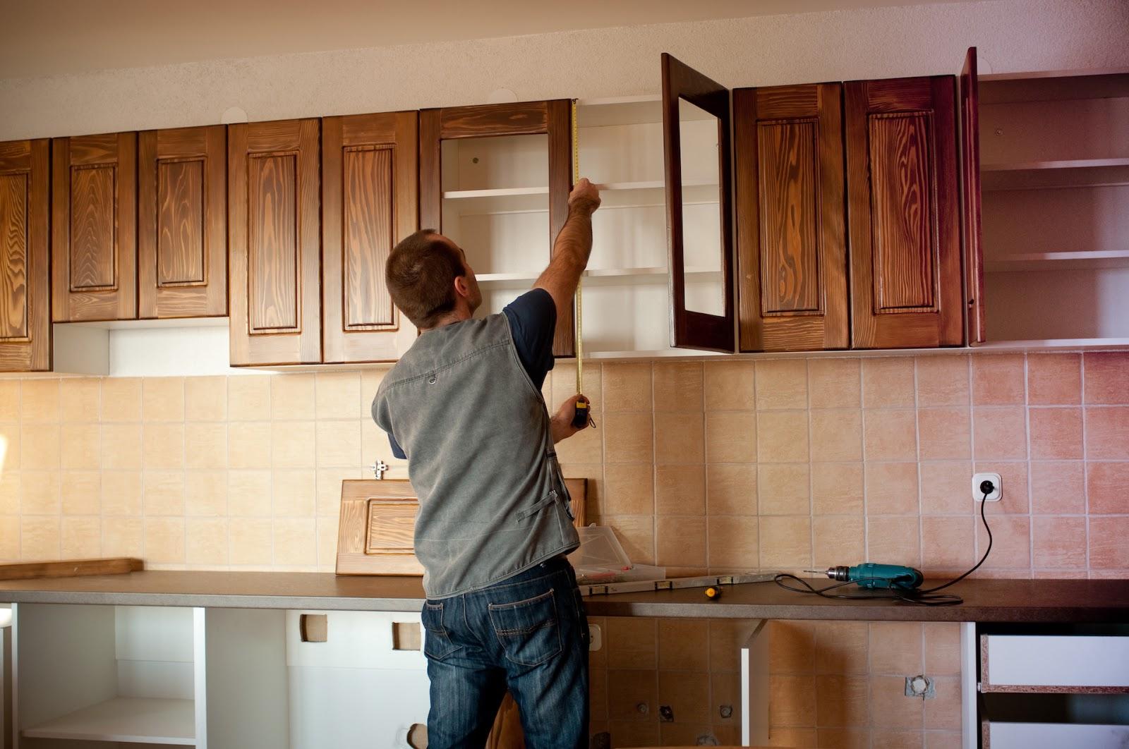 Man measuring cabinets