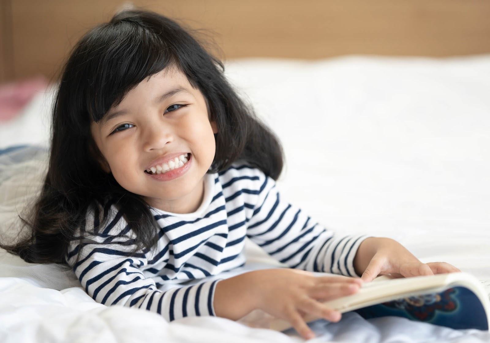 Young asian girl smiling on a bed with her book