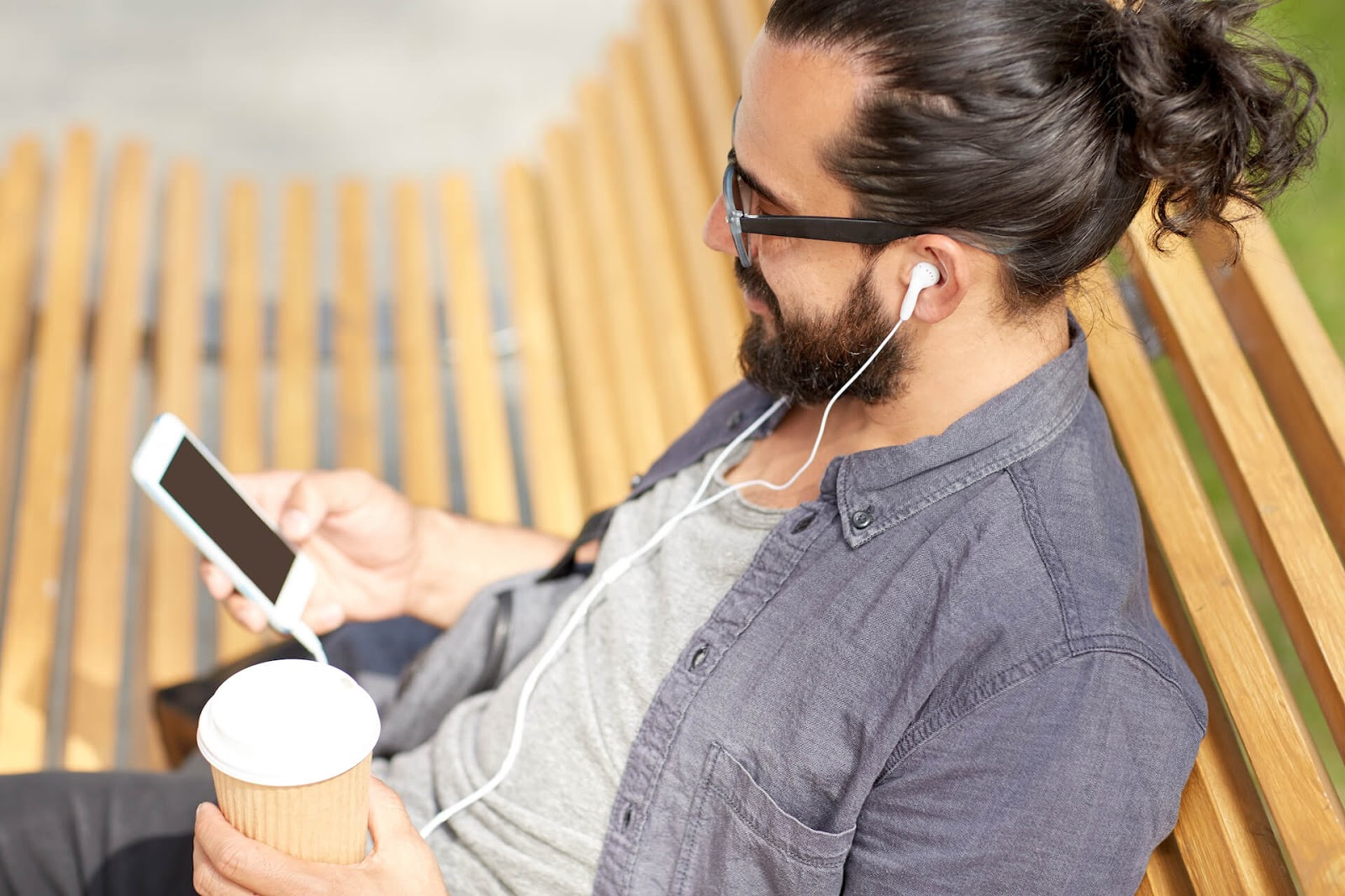 Man sitting on a bench with his headphones, looking at his phone