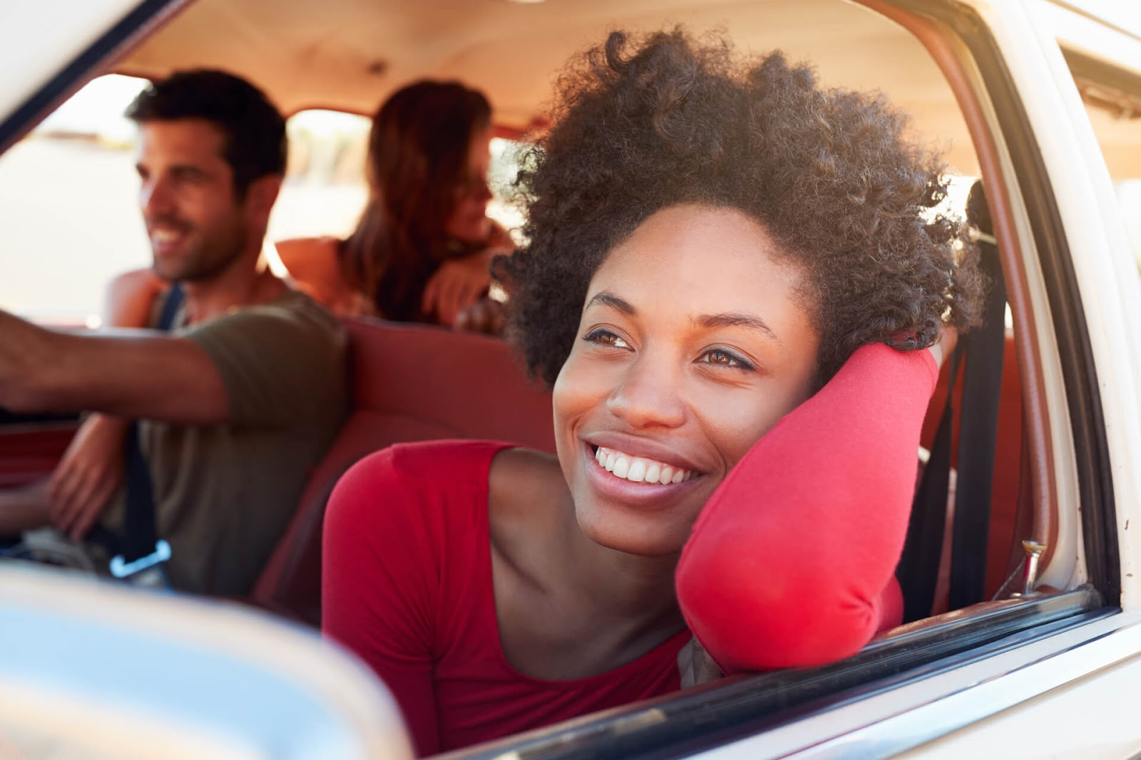 Woman enjoying a car ride with some friends