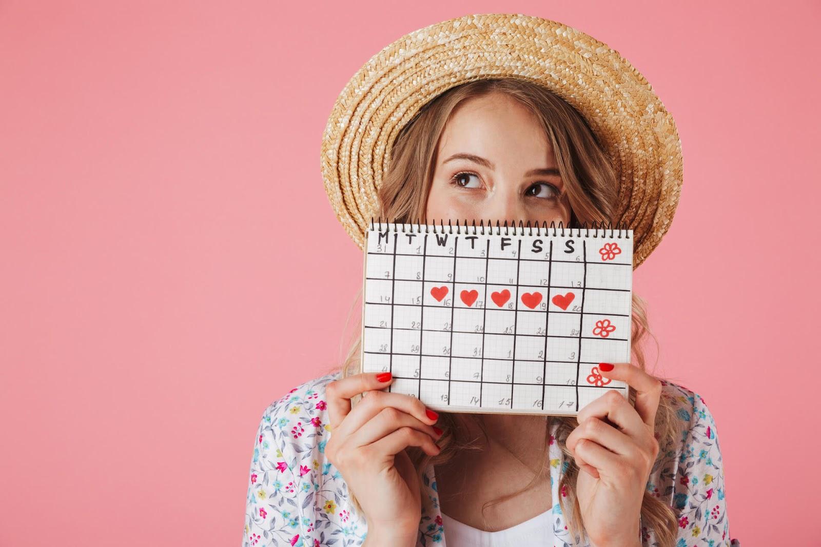 Woman holding up her menstrual calendar