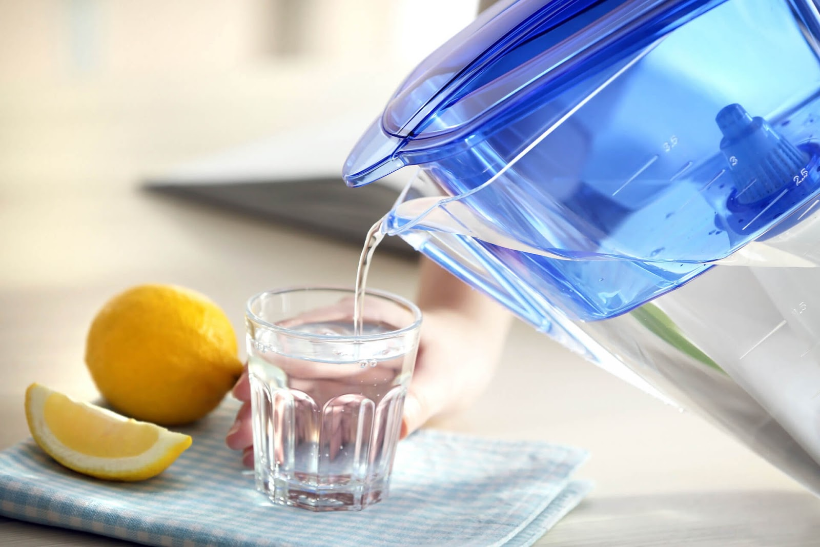 Someone pouring water from a pitcher into a cup with some lingering lemons nearby