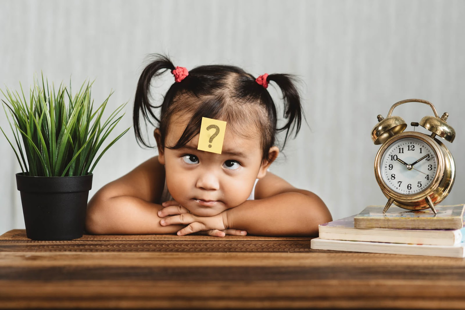 Young girl with a question mark stuck to her forehead
