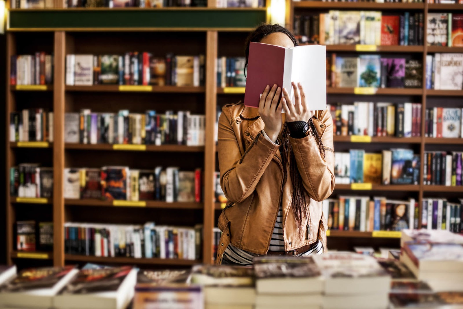 Woman holding a book in front of her face in a bookstore