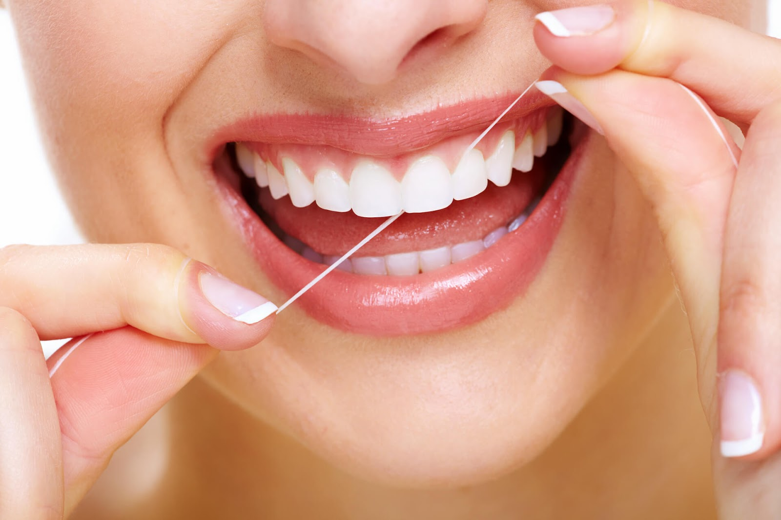 Close up of woman flossing her perfectly straight, white teeth