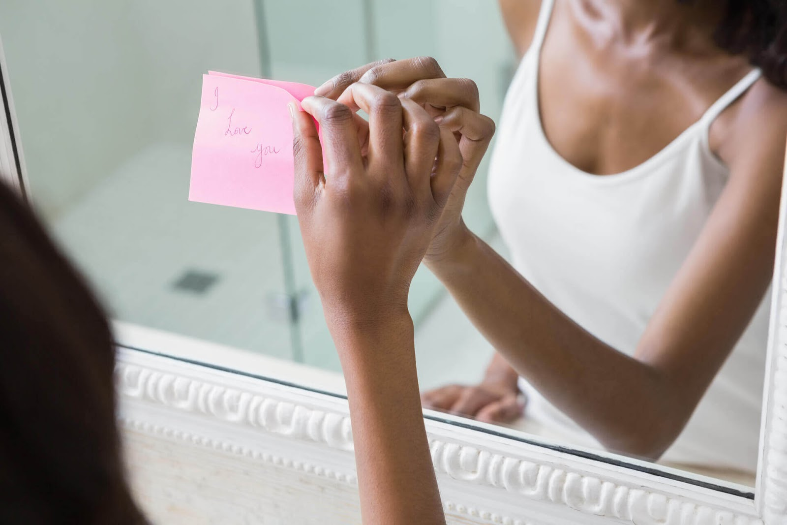 "Woman putting an ""I love you"" post-it on the mirror"