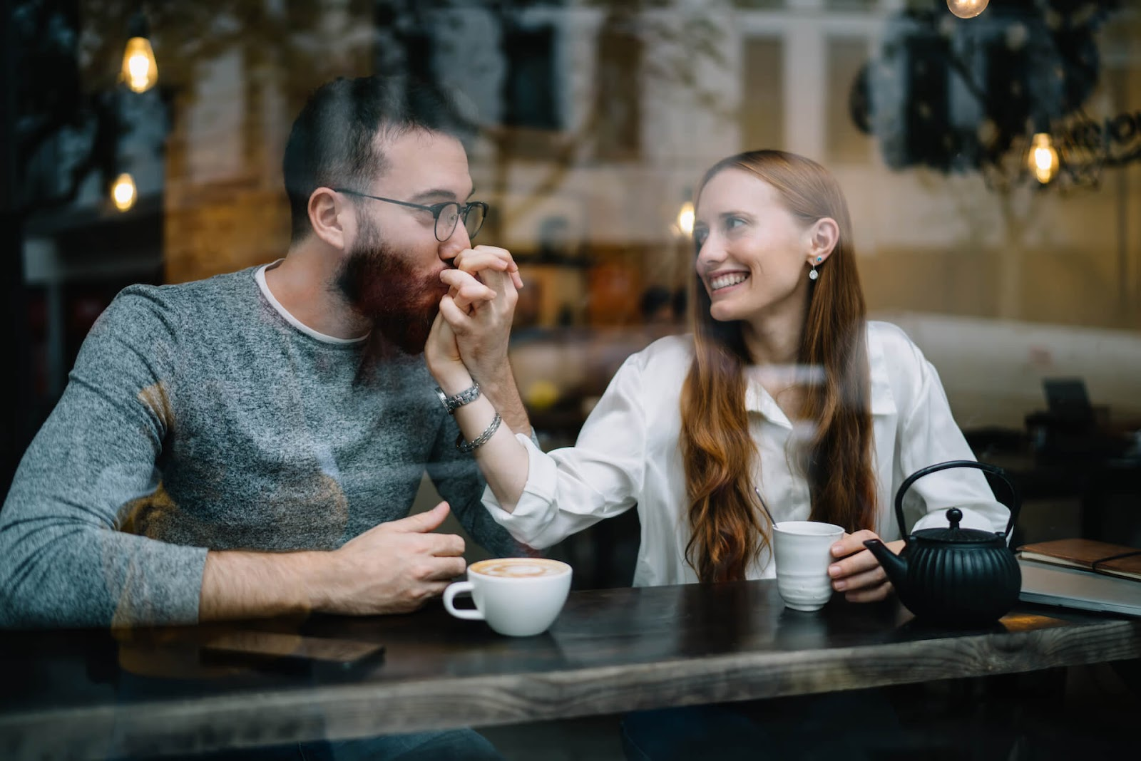 Man kissing woman's hand in a coffee shop