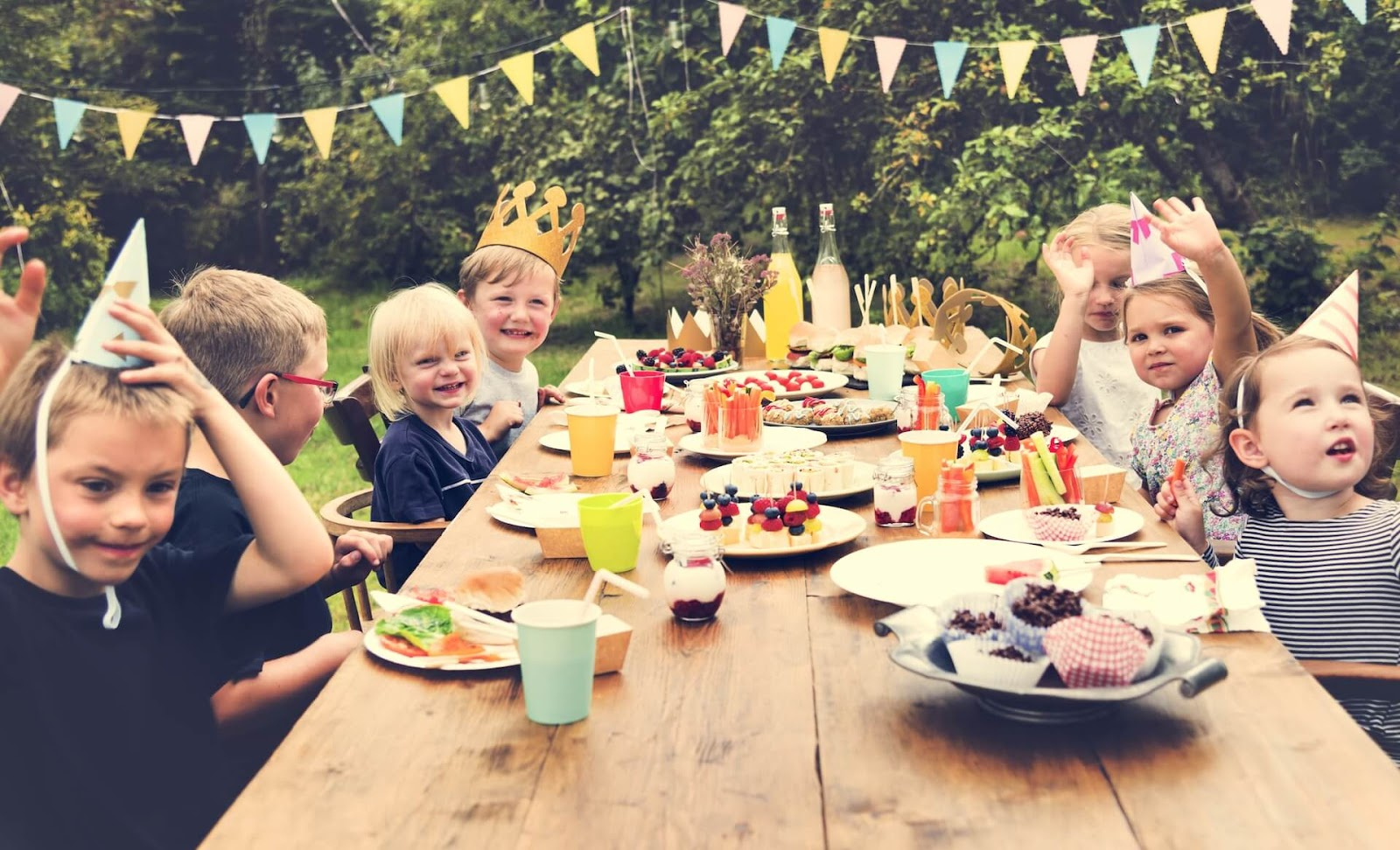 Kids sitting around a table at a backyard birthday