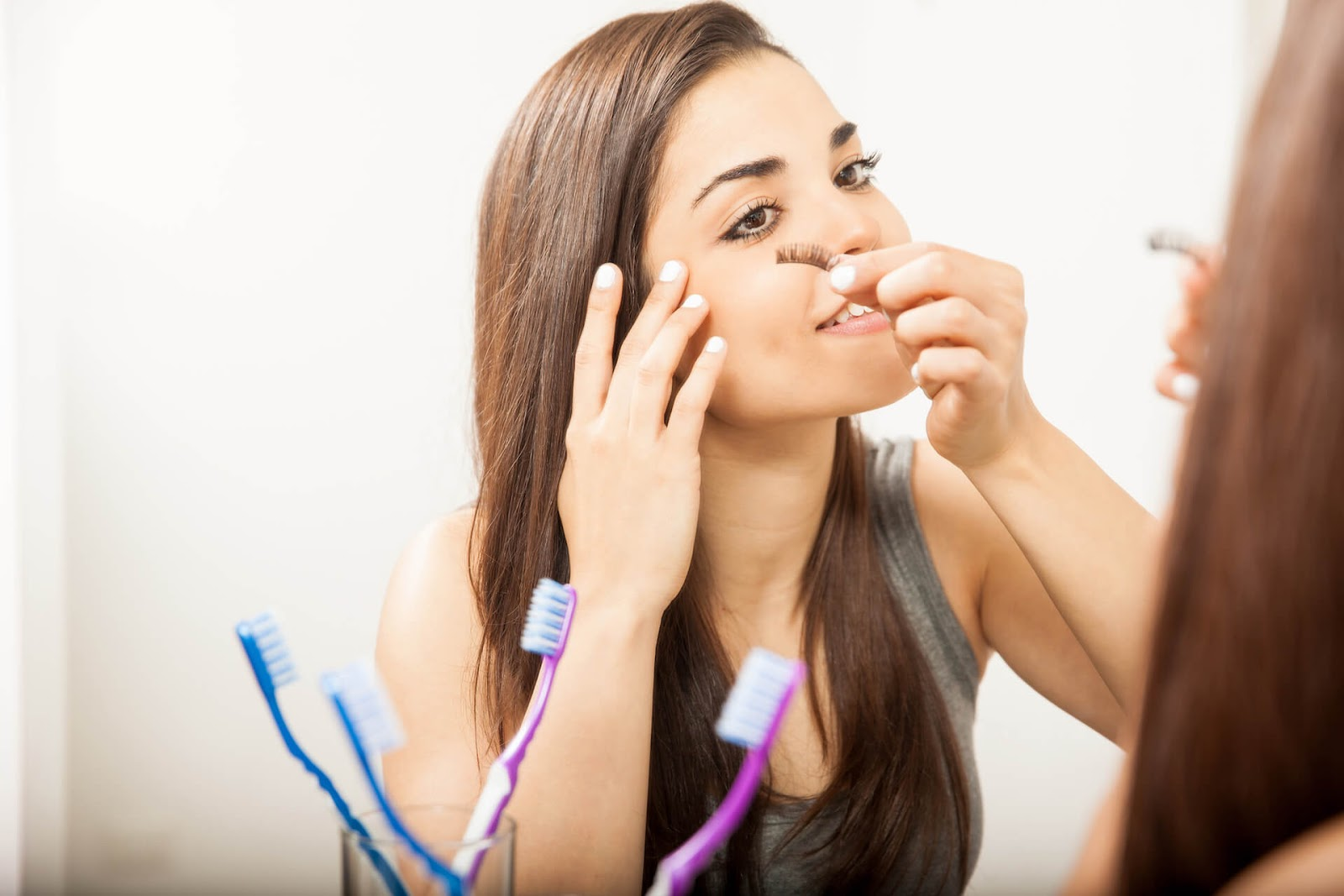 Lady applying some fake eyelashes with her fingers