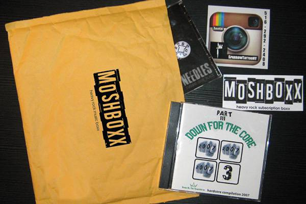 Contents of a MosBoxx subscription box including a cd, and some stickers