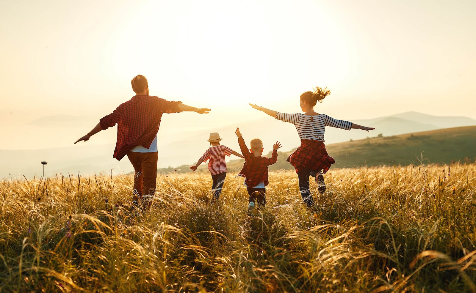 Family frolicking through a field together