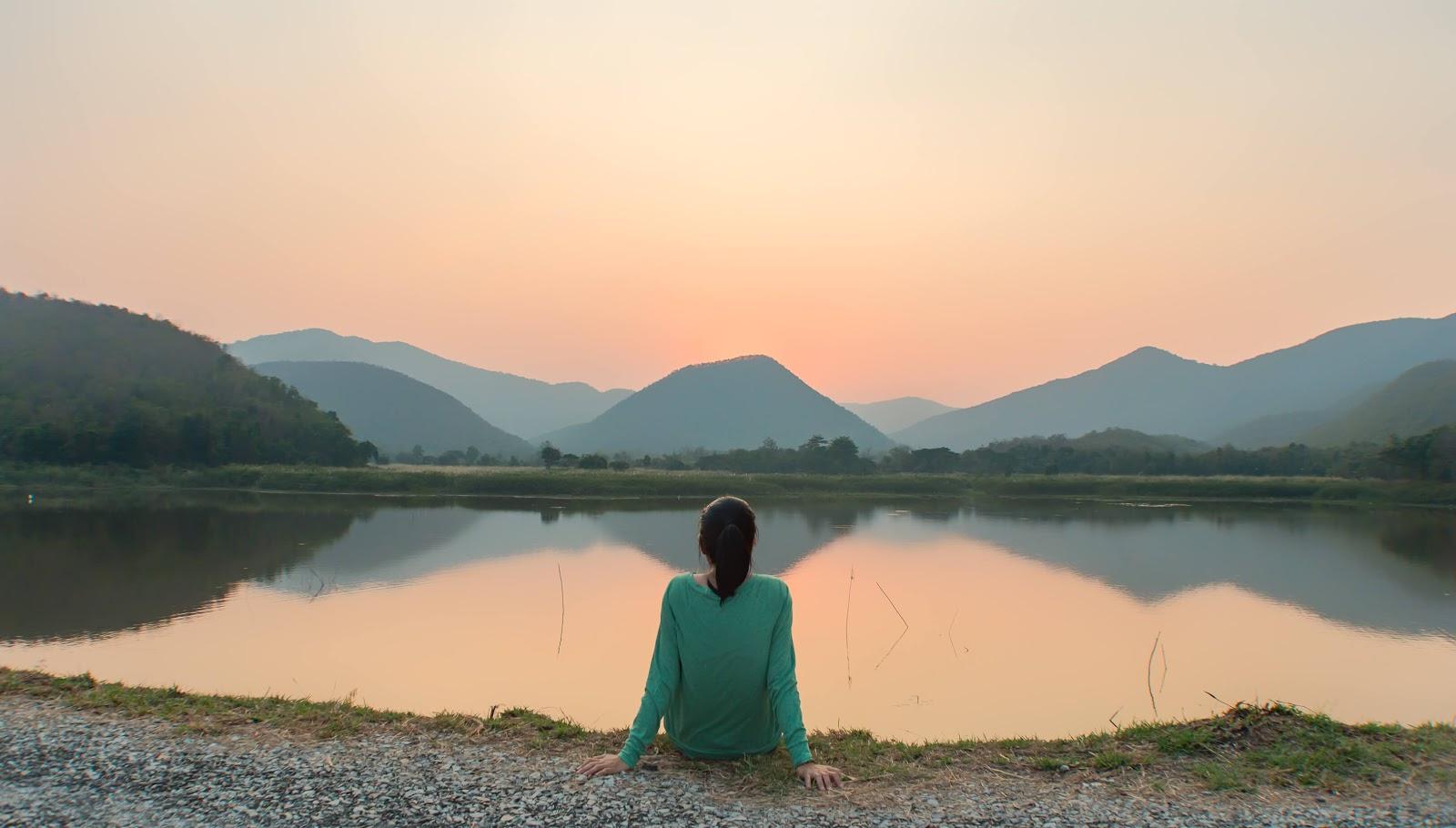 Woman enjoying a serene lake and mountain scene