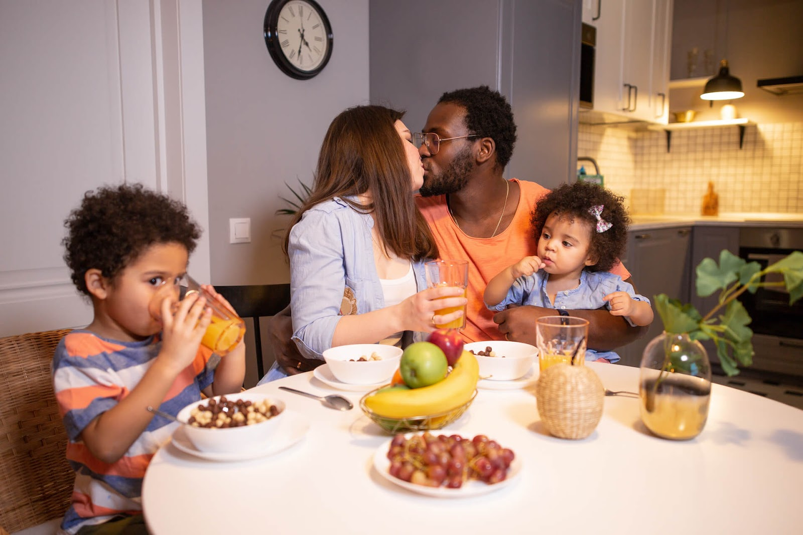 Man and woman kissing at the breakfast table with their children