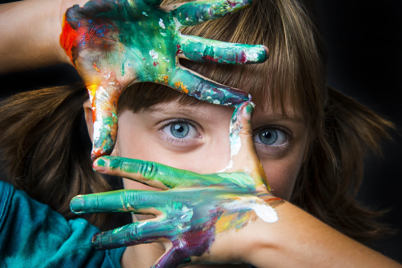 Young girl with paint all over her hands making a frame over her eyes