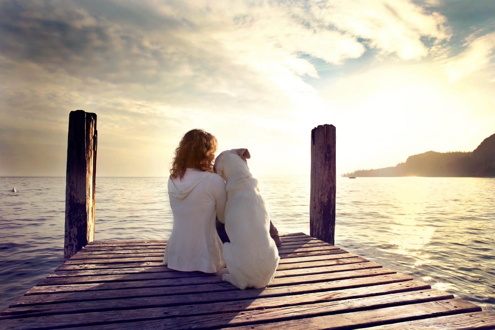 Woman snuggling with her dog on a dock overlooking a beautiful view