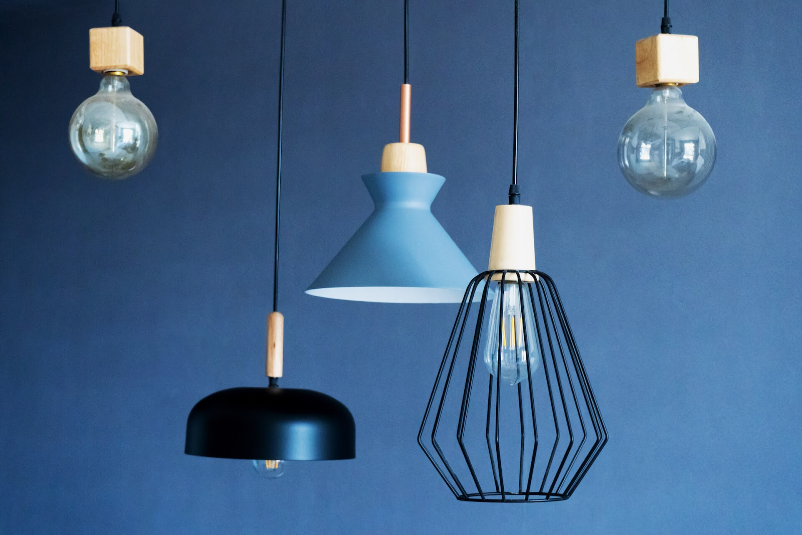 Different hanging ceiling lights against a blue backdrop