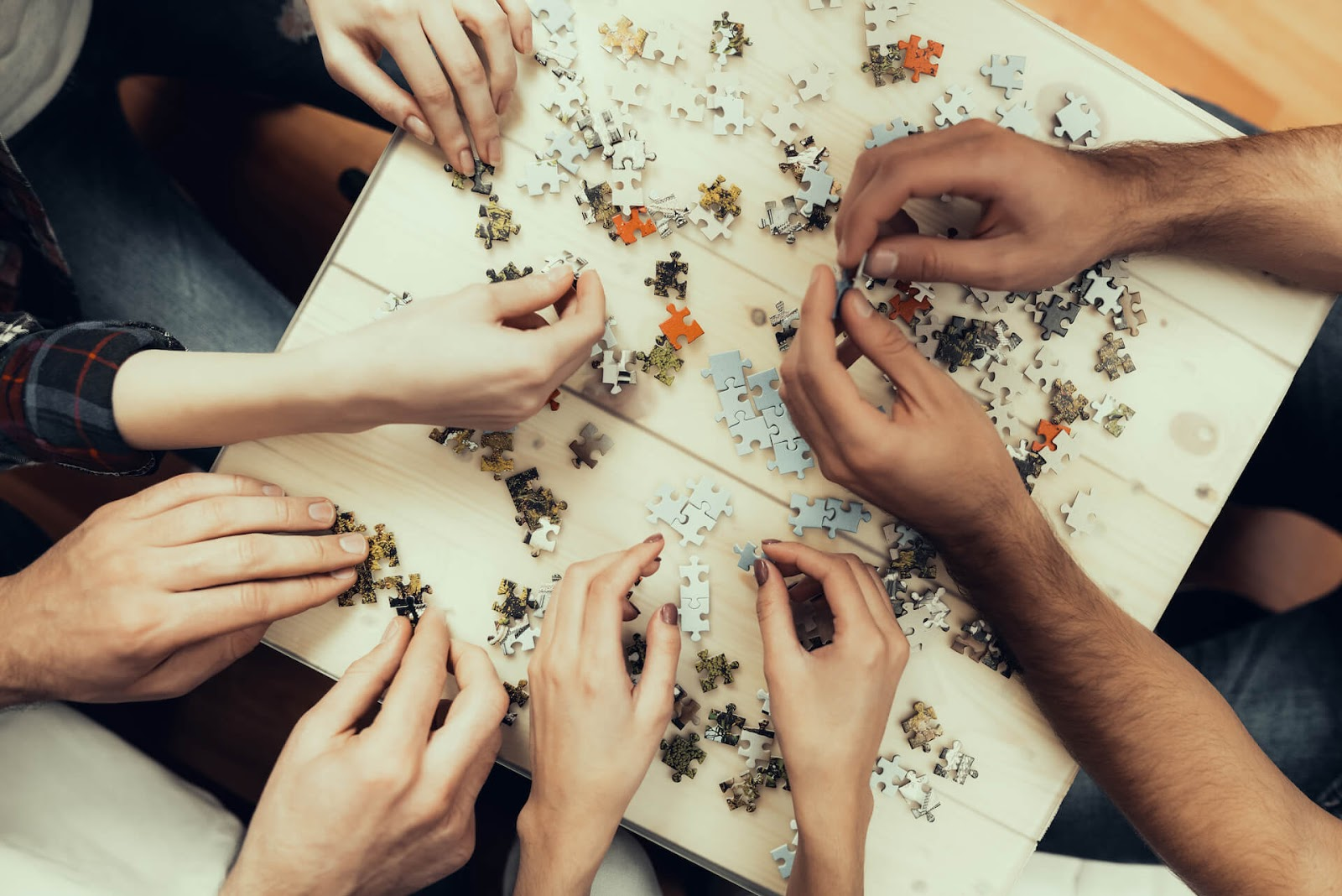 birds-eye view of friends putting a puzzle together
