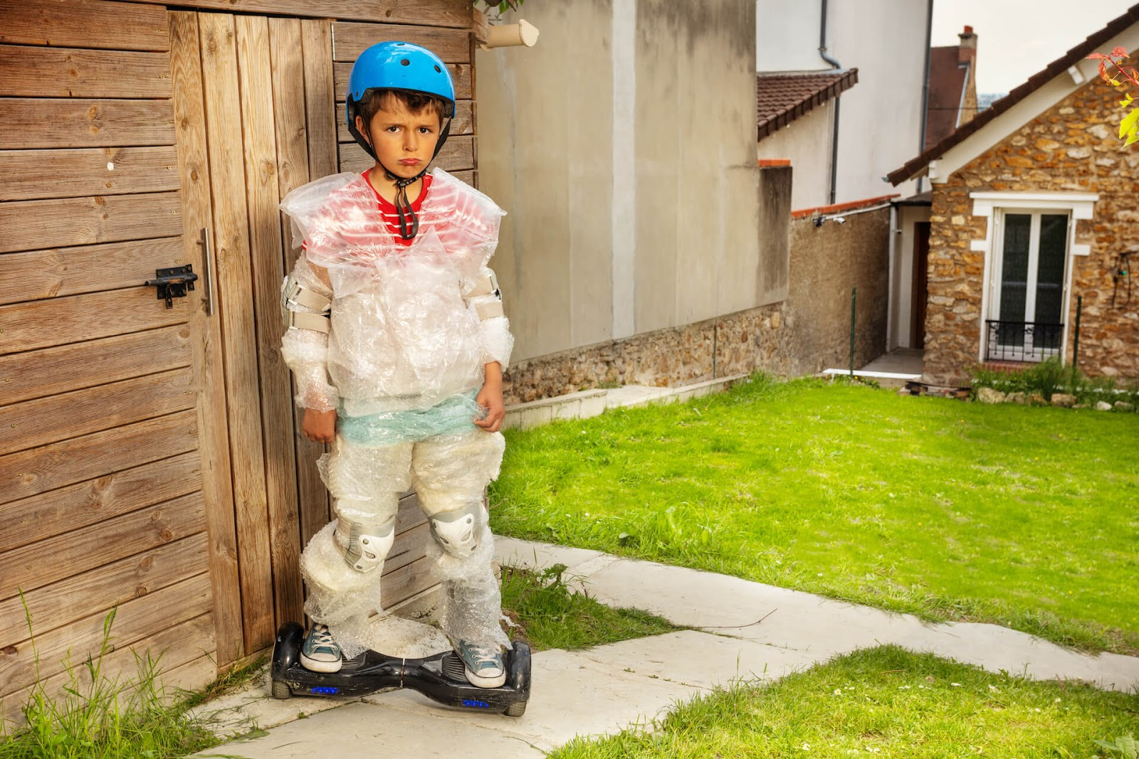 Boy trying to skateboard but covered in bubble wrap