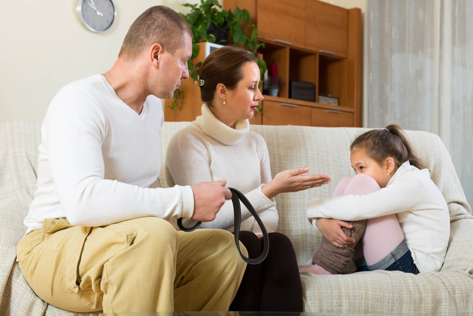 Parents lecturing their daughter on the couch