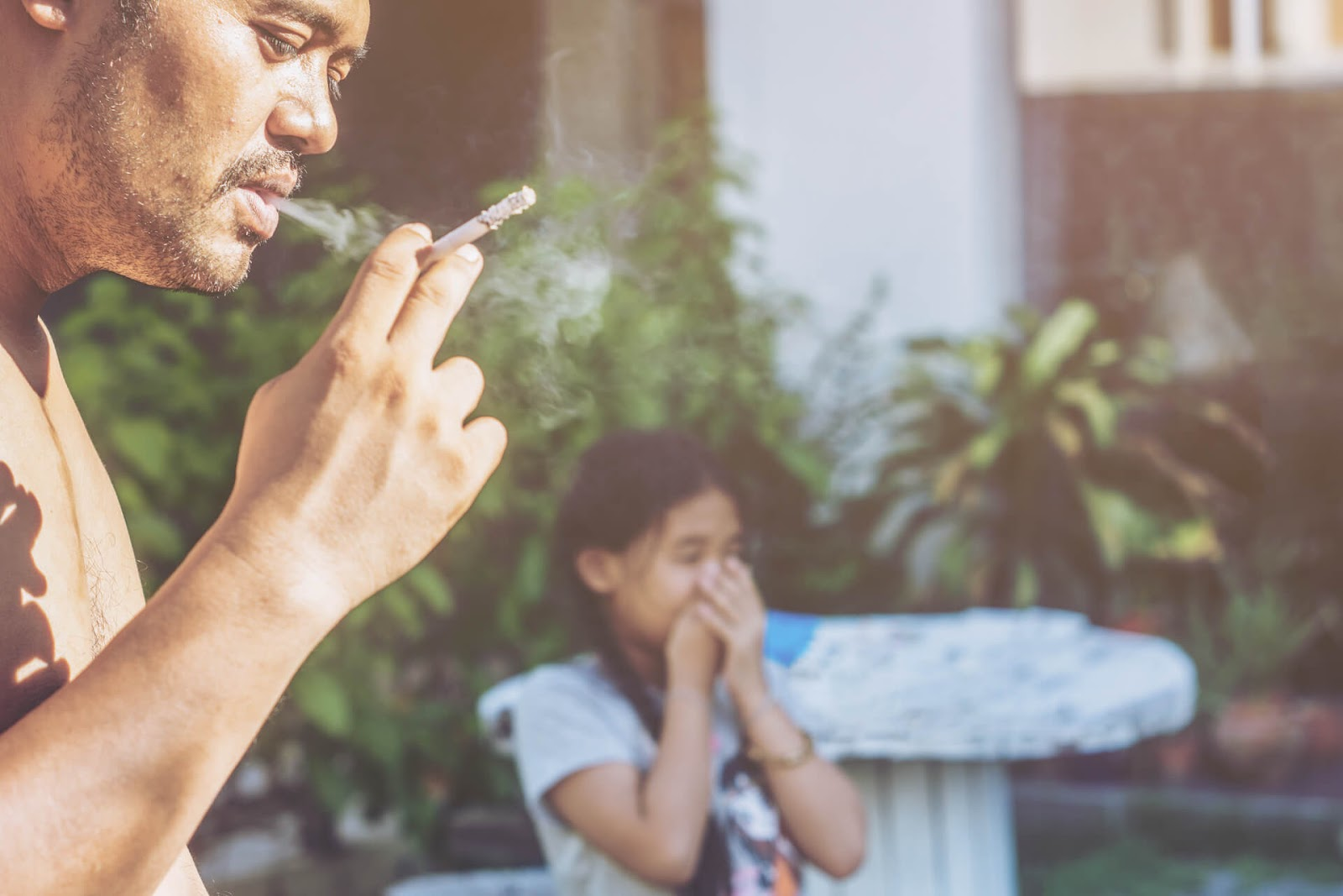 Father smoking a cigarette with daughter in the background