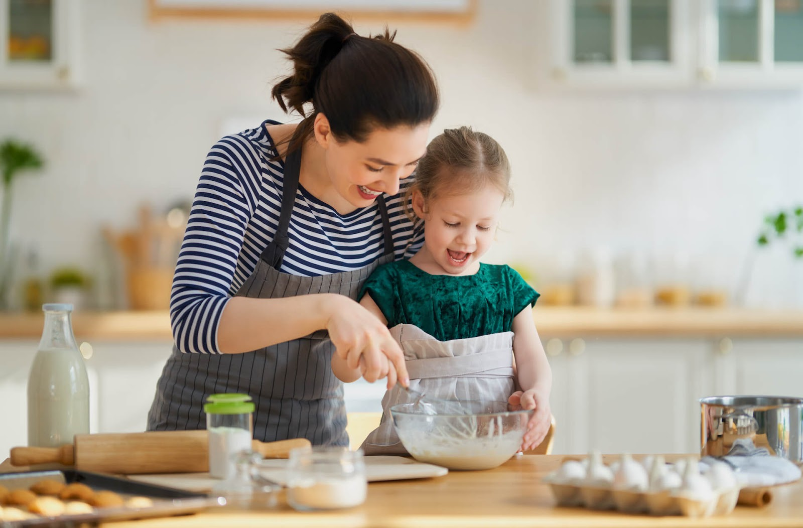 Mom and daughter baking together happily