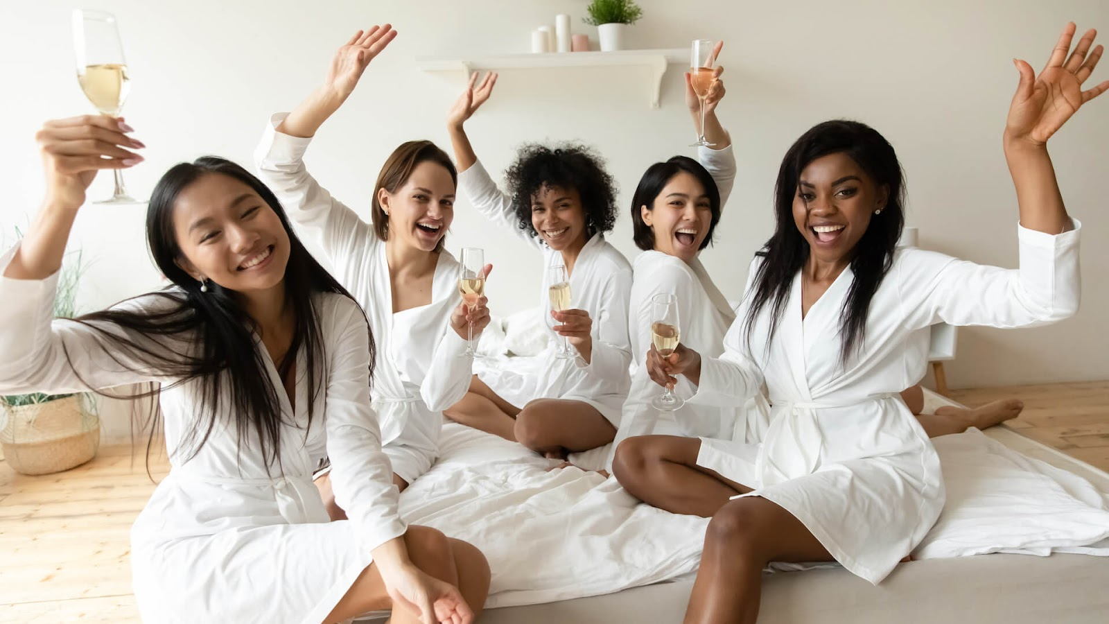 Bridal party enjoying cocktails in matching white robes